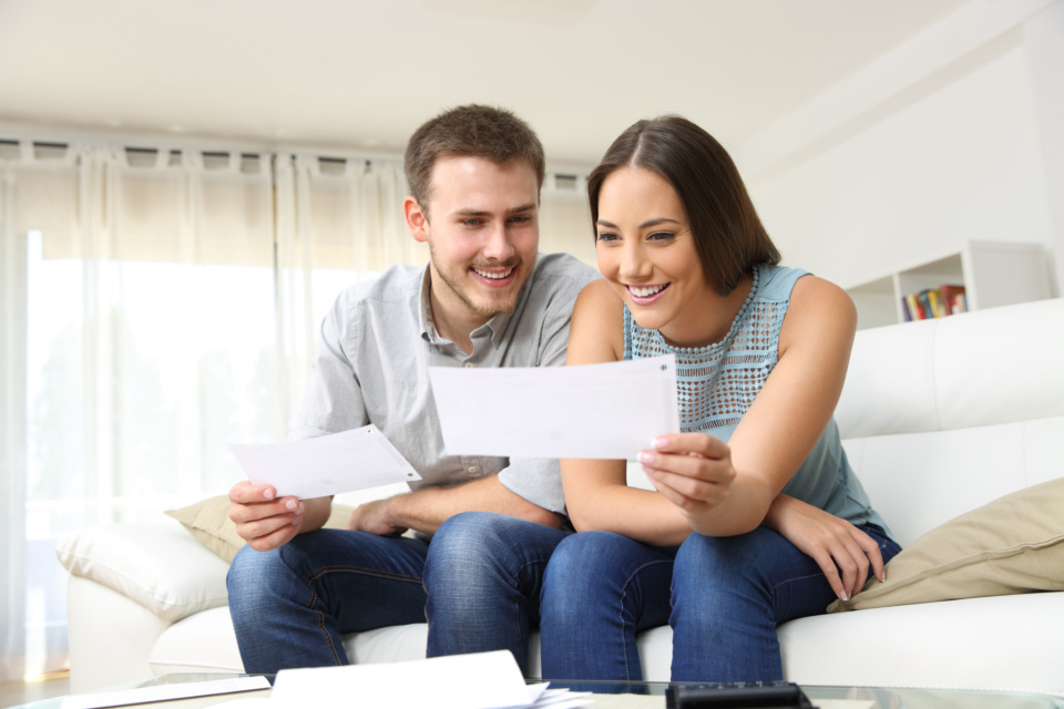 Happy couple looking and checking bills at home 1219963854 2125x1416