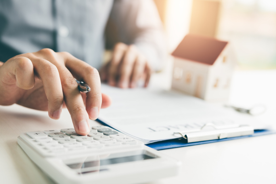 Home agents are using a calculator to calculate the loan period each month for the customer 1075993466 2125x1416