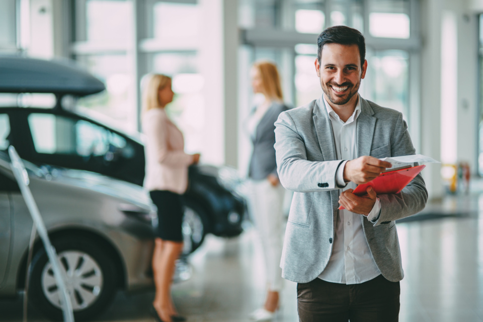 Successful businessman in a car dealership sale of vehicles to customers 1172428955 2125x1416