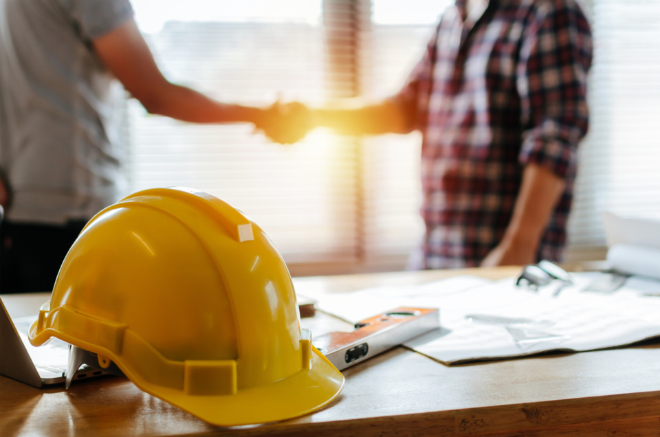 Yellow safety helmet on workplace desk with construction worker team hands shaking greeting start up plan new project contract in office center at construction site partnership and contractor concept 1153235950 2131x1411